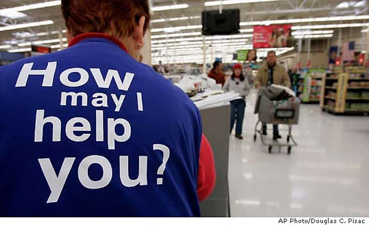 Customers at a Wal-Mart store head to the checkout lines past a worker with the company's motto on the back of her vest Sunday, Nov. 13, in Salt Lake City. Wal-Mart Stores Inc., the world's largest retailer, said Monday, Nov. 14, 2005, its earnings rose 3.8 percent in the third quarter as sales grew 10 percent. (AP Photo/Douglas C. Pizac)