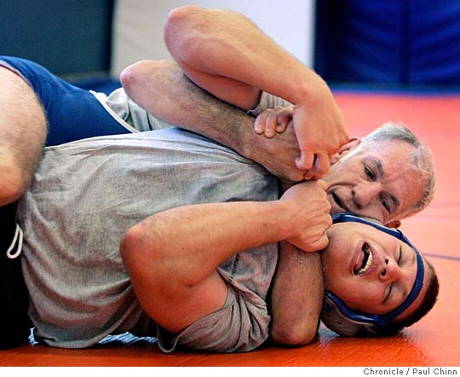 Coach Jim Lucas, a wrestler at San Jose State from 1971-1974, teaches a move to Joseph Bruzzone when the SJSU wrestling club practiced on campus on 11/19/05 in San Jose, Calif. San Jose State used to have one of the best wrestling programs around. But 20 years ago, the program was cut due to budget constraints. Four years ago, former Spartan Jim Lucas revived the program at the club level. Since then, the team has won a conference championship and produced All-American wrestlers  PAUL CHINN/The Chronicle Photo: PAUL CHINN