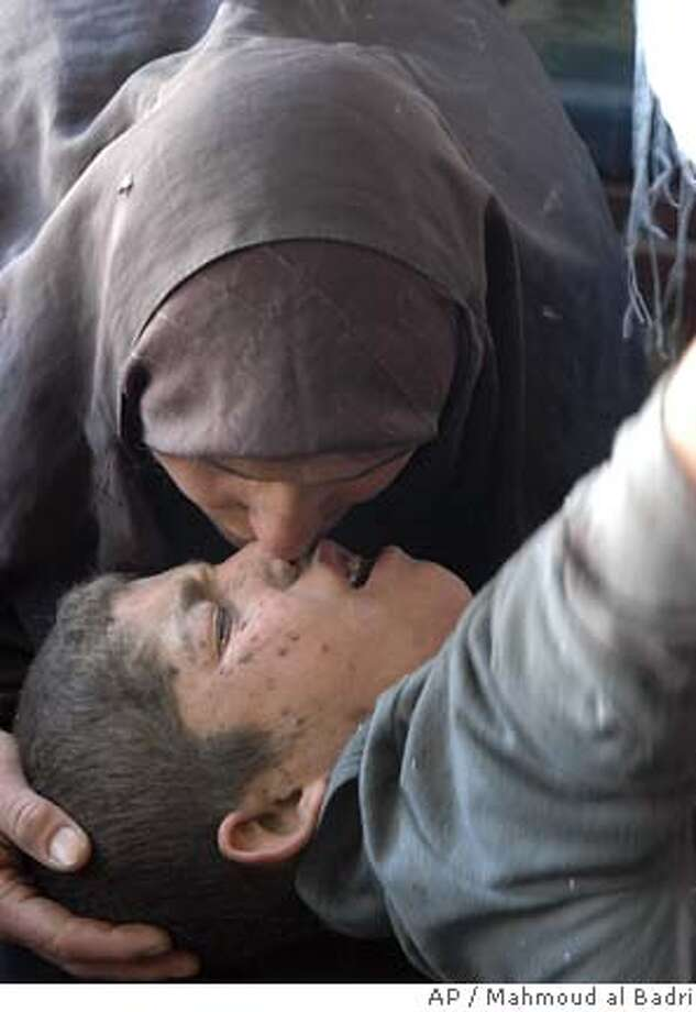 A boy is consoled by his mother as he is treated at Yarmouk hospital, in Bahdad, Iraq, Thursday, Nov. 24, 2005. A car bomb detonated outside Mahmoudiya hospital in the center of a town south of Baghdad on Thursday, killing 30 and wounding 35, a doctor said. Among the dead were four police guards, three women and two children, said Dr. Dawoud al-Taie, the director of the Mahmoudiya hospital. Medical condition of this boy is unknown. (AP Phoot/Mahmoud al Badri) Photo: MAHMOUD AL BADRI
