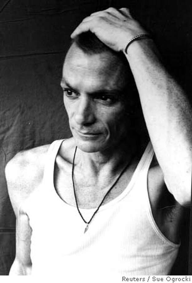 "Singer-songwriter Chris Whitley is seen in this undated handout photograph Whitley who emerged from obscurity in 1991 with his debut album ""Living with the Law,"" has died at age 45, after a brief battle with lung cancer, in his hometown of Houston, Texas on November 20, 2005, his label said on November 22, 2005. Whitley earned critical and commercial success for the blues-drenched album, ""Living with the Law."" The title track was a minor hit, and Tom Petty and Bob Dylan hired him to open their tours. NO ARCHIVE REUTERS/Sue/Handout Photo: SUE OGROCKI"