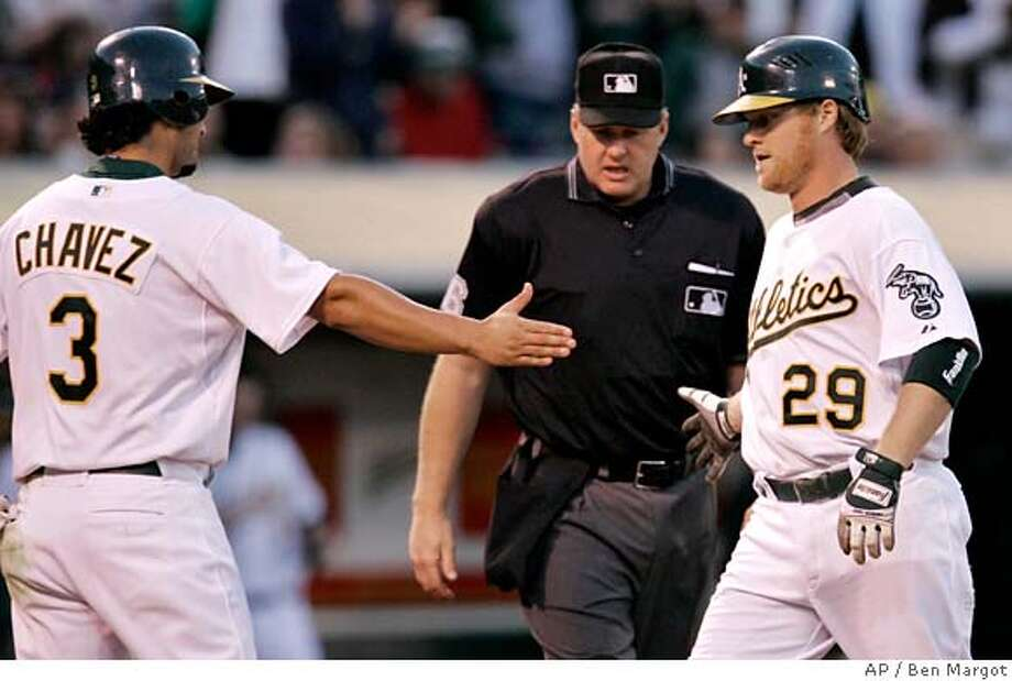 Oakland Athletics' Eric Chavez (3) congratulates Dan Johnson (29) after Johnson's two-run home run off San Francisco Giants' Barry Zito in the third inning of a baseball game Friday, May 18, 2007, in Oakland, Calif. (AP Photo/Ben Margot) Photo: Ben Margot