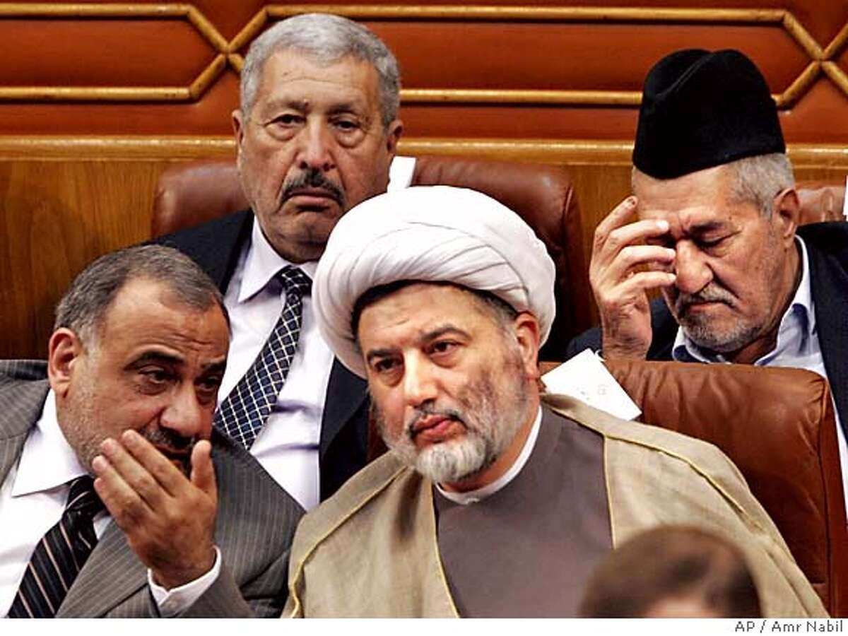 Iraqi Shiite Sheik Humam Hammoudi, who chairs the delegations of the Supreme Council for the Islamic Revolution in Iraq at the Arab League meetings, right, listens to Iraqi Vice President Adel Abdul Mehd, left, as top Sunni politician Adnan al-Dulaimi, the leader of the General Conference of the Iraqi People, background right, looks on during the opening session of the three-day preparatory meeting of the Iraqi reconciliation conference at the Arab league in Cairo, Egypt, Saturday, Nov.19, 2005. Iraqi leaders assembled in Cairo on Saturday in an effort to patch over ethnic and religious fault lines, with the chief of the Arab League warning against allowing the country to slip into