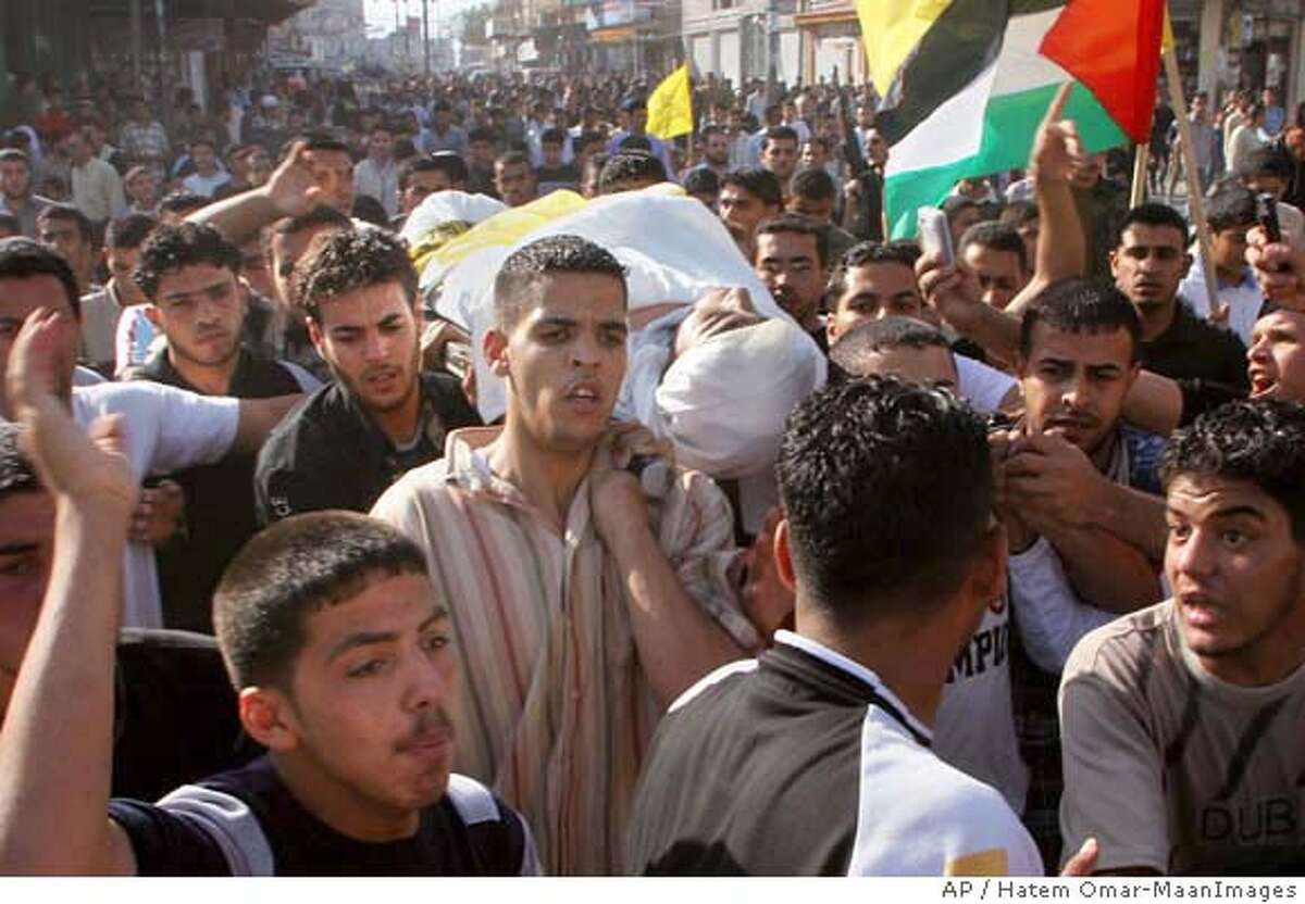 Palestinian mourners carry the body of a security force officer loyal to the Fatah Movement killed during an attack by Hamas militants, during his funeral in Gaza City,Tuesday, May 15, 2007. Hamas gunmen on Tuesday ambushed rival Fatah forces near a key crossing along the Israeli border, killing eight people in the deadliest battle yet in three days of factional fighting. The incident briefly drew Israeli gunfire, threatening to drag Israel into the conflict. (AP Photo/Hatem Omar-MaanImages)