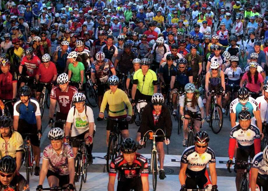 Riders begin the Tour de Houston on Smith Street Sunday. A spokeswoman with the city says many people took part in this year's ride because it was a fundraiser for area parks and reforestation efforts. Photo: Cody Duty / © 2011 Houston Chronicle