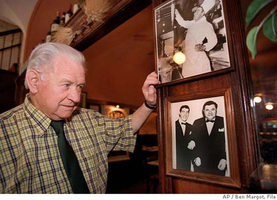 """Dante Benedetti looks at photographs of Joe DiMaggio with Babe Ruth hanging on the wall of his restaurant New Pisa in the North Beach section of San Francisco Monday, March 8, 1998. Benedetti , who played baseball with DiMaggio as a child, recalled he was """"always picked first for teams,"""" and that he was """"the best baseball player that ever lived."""" Baseball legend Joe DiMaggio died earlier this morning. (AP Photo/Ben Margot) Photo: BEN MARGOT"""