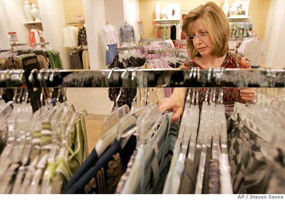 Shopper Debbie Mirabello, of Woburn, Mass., examines clothing on a rack while shopping at a Macy's department store, in Newton, Mass., Wednesday, May 9, 2007. Stocks retreated Thursday, May 10, 2007, after many of the nation's major retailers reported weak April sales, raising concerns about consumer spending in the coming months. (AP Photo/Steven Senne) Photo: Steven Senne