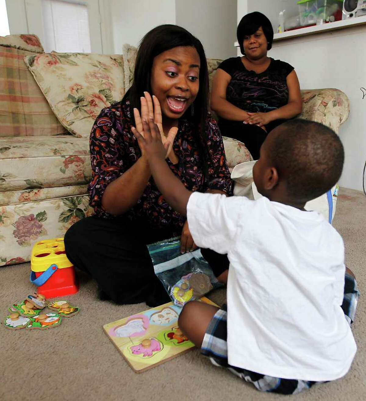Andrew Love, 2, high-fives Obehi Oriakhi, a speech therapist with an early childhood intervention program, during a speech therapy lesson as his mother, Raykira Nelms, watches.