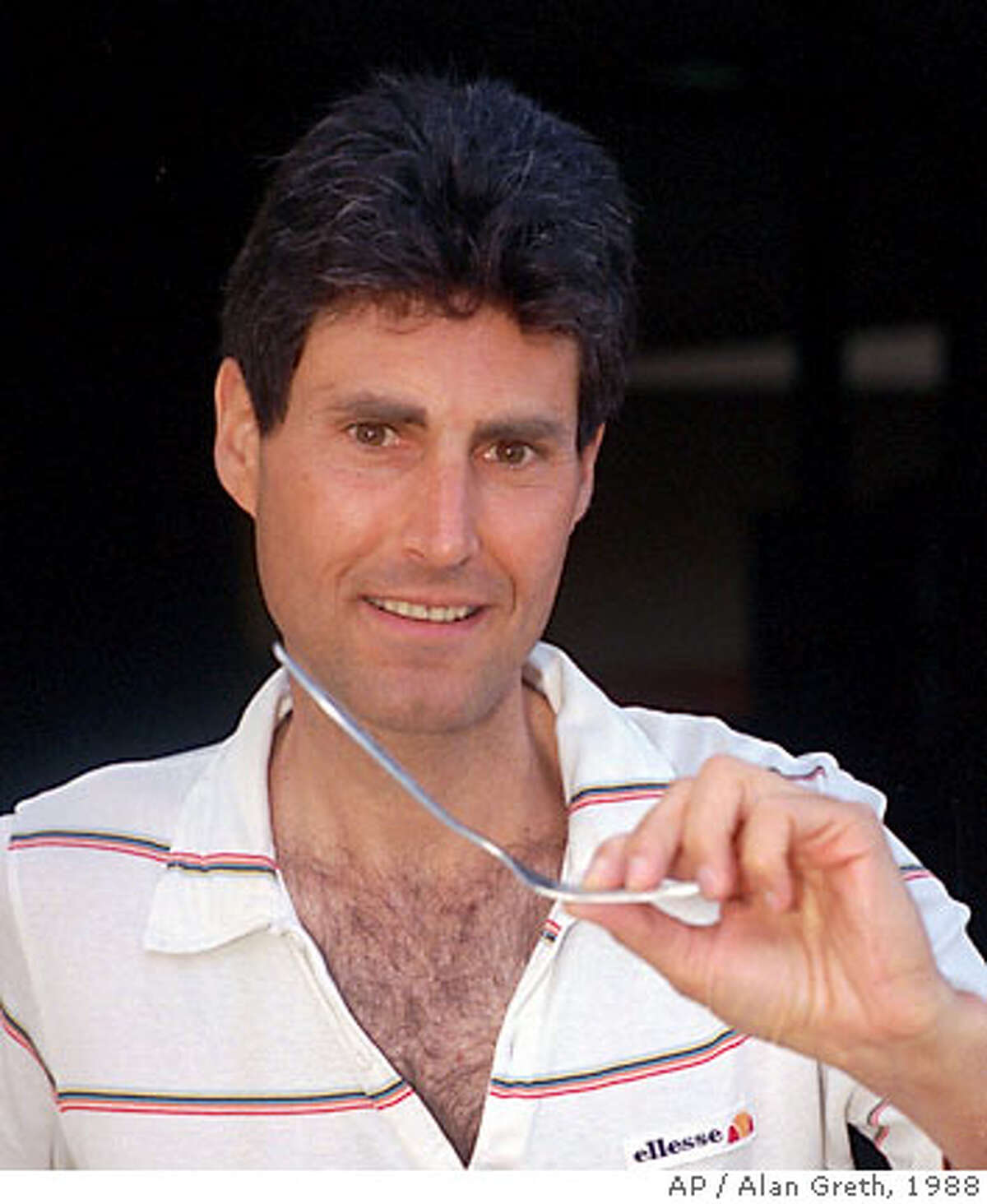 """FILE--Author and psychic phenomena expert , shown in this May 14, 1988 file photo, displays the bent fork he was observed causing to bend while holding in only one hand in Pasadena, Calif. Geller's powers failed him Friday, Dec. 9, 1994 when it came to persuading a court to lift a $149, 000 fine. Geller's lawyer, Richard Winelander said Geller's original lawyer was responsible for missing deadlines and failing to repond to the organization that was suing. """"He's taking the brunt of the burden for the sins of his attorney,"""" said Winelander. (AP Photo/Alan Greth) MAY 14, 1988 FILE PHOTO ALSO RAN: 10/22/1999 (CF, CC1)"""