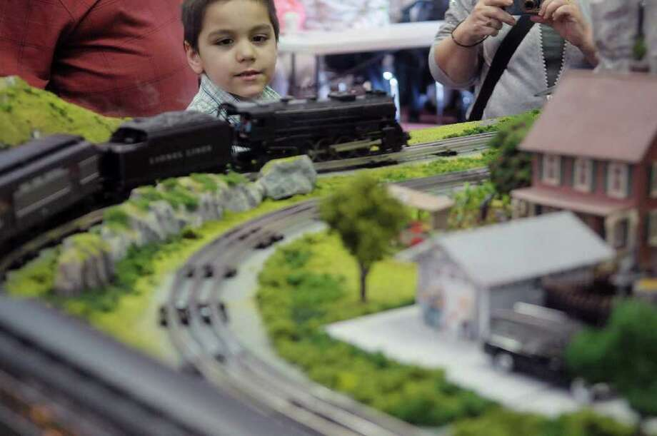 Tyler Mena, 6, from Stockport, NY watches a model train go by at the O gauge model train working display of the Empire and Easter Division of the Toy Train Operating Society, seen here at the Mountain Toy and Railroad Club Albany Toy and Train Show at the Polish Community Center on Sunday, March 18, 2012 in Albany, NY.  The Mountain Toy and Railroad Club, which is out of Hudson, holds four of the shows a year, two in Albany and two in Hudson.  The shows include displays of model trains and vendors that buy sell and trade model trains and toys.  The club's next show will be November 18, 2012 in Albany.   (Paul Buckowski / Times Union) Photo: Paul Buckowski