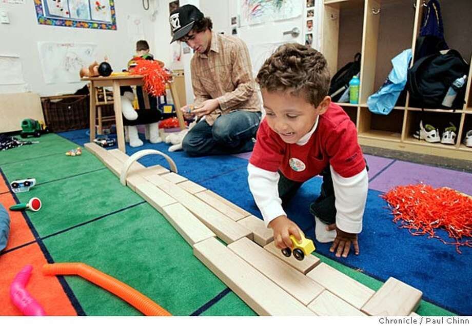 Omar Carr-Wallace plays with a toy car with teacher Shawn Mowell (background) in the KidSpace child care center at the Lesbian Gay Bisexual Transgender center in San Francisco. Photo: PAUL CHINN