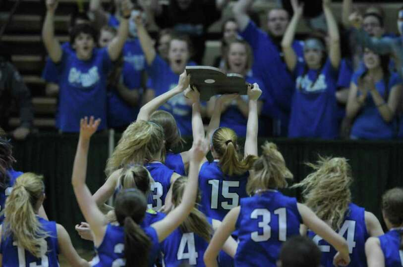 Hoosic Valley High School girls carry their state championship plaque across the basketball court to