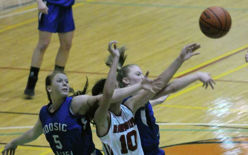 Alicia Lewis, left, and Cassidy Chapko, right, of Hoosic Valley High School fight for a rebound agai