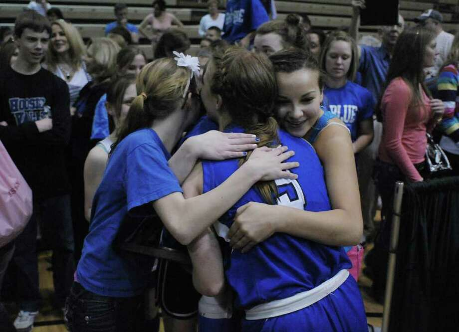Alicia Lewis, center, of Hoosic Valley High School is hugged by fellow students after  Hoosic Valley won the Class C girls' basketball final against Randolph Central School on Sunday, March 18, 2012 at the McDonough Sports Complex at Hudson Valley Community College in Troy, NY.  (Paul Buckowski / Times Union) Photo: Paul Buckowski