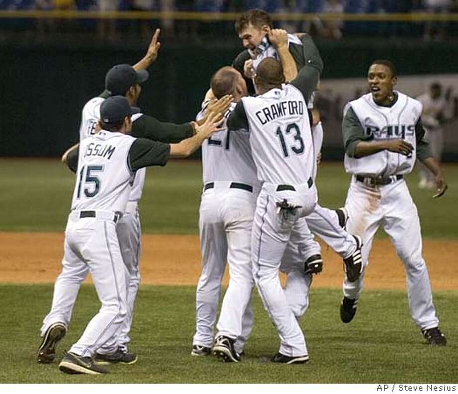 Tampa Bay Devil Rays' Casey Fossum (15), Carl Crawford (13), Ty Wigginton (21) and B.J. Upton, right, mob Brendan Harris, top, after his game-winning RBI single off Oakland Athletics reliever Jay Marshall during the 12th inning of a baseball game Saturday, May 5, 2007, in St. Petersburg, Fla. Tampa Bay won 3-2. (AP Photo/Steve Nesius) Photo: Steve Nesius