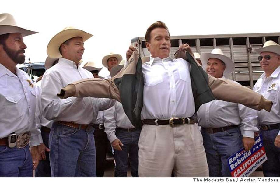 """Members of the Merced County Sheriff Posse present California Gov. Arnold Schwarzenegger with a jacket embroidered with his name making him an """"Honorary Member"""" of the posse following a campaign speech in Oakdale, Calif., on Sunday, Nov. 6, 2005. The posse give Schwarzenegger the jacket to thank him for his assistance - both financial and influencial - for their inclusion as one of two equestrian units from California to ride in the Presidential Inaugauration Parade in Washington this past January. Immediately to the left of Schwarzenegger is Merced Sheriff Mark N. Pazin. (AP Photo/The Modesto Bee, Adrian Mendoza) Photo: ADRIAN MENDOZA"""
