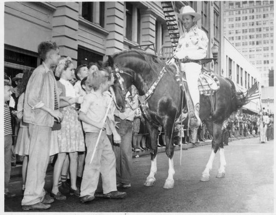 Gene Autry at the Houston Fat Stock Show, 1/29/47.      HOUCHRON CAPTION (10/03/1998):   Gene Autry and his horse entertain children on the streets of downtown Houston during the 1947 Houston Fat Stock Show and Rodeo parade.     HOUCHRON CAPTION (02/10/2002):   Movie star Gene Autry and his horse entertain children in downtown Houston on Jan. 29, 1947, during what was then called the Houston Fat Stock Show and Rodeo parade.