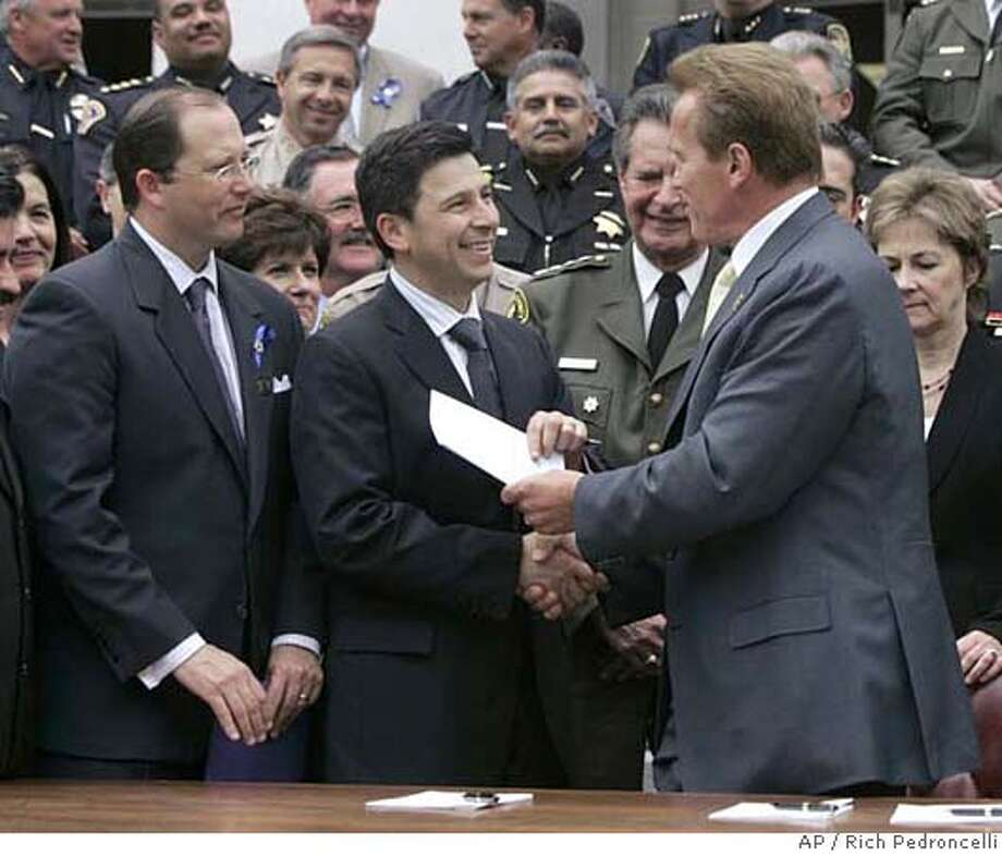 Gov. Arnold Schwarzenegger, right, gives Assembly Speaker Fabian Nunez, D-Los Angeles, second from left, a copy of the prison-reform plan he signed, as Assembly Minority Leader Mike Villines, R-Clovis, left, looks on at the Capitol in Sacramento, Calif., Thursday, May 3, 2007. The $.78 billion deal will add 53,000 prison and country jails beds and improve rehabilitation and drug treatment programs and vocational education for inmates.(AP Photo/Rich Pedroncelli) Photo: Rich Pedroncelli
