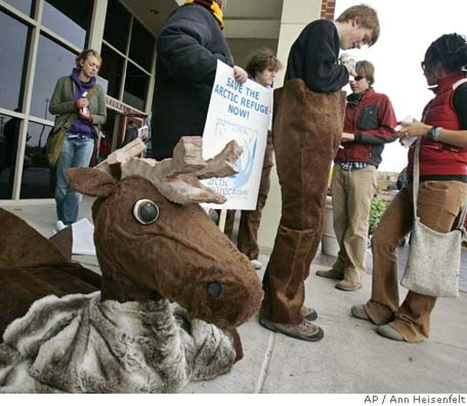 John Weber, center, a freshman at the University of Minnesota and the legs for a moose outfit, talks with another student after taking part in the Emergency Campaign for America's Priorities coalition protest outside Sen. Norm Coleman's office in St. Paul, Minn., Thursday, Nov. 3, 2005. The coalition demands that Coleman vote against a bill allowing drilling in the Alaska National Wildlife Refuge and budget cuts to programs such as Medicaid. Weber, whose brother is a member of the Alaska Coalition, said he heard about attempts to push the ANWR bill into the budget and felt like something had to be done, so he donned the moose costume and took part in the demonstration. (AP Photo/Ann Heisenfelt) STAND ALONE PHOTO Photo: ANN HEISENFELT