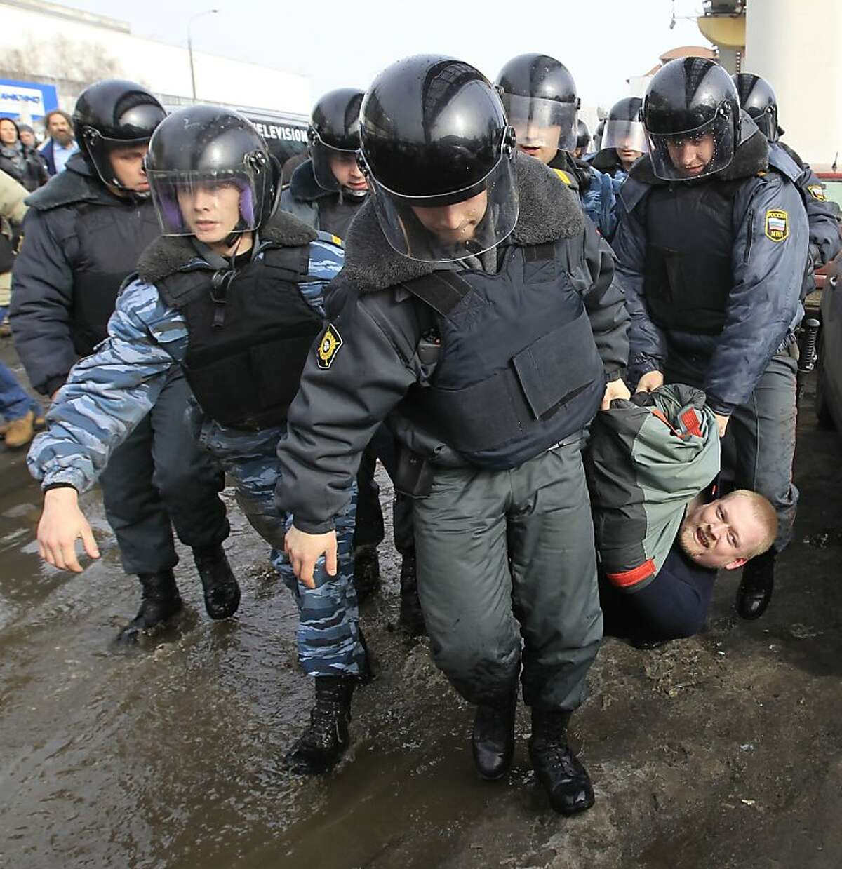 Police officers detain a protester outside the Kremlin-loyal NTV television station in Moscow, Sunday, March, 18, 2012. The NTV documentary program