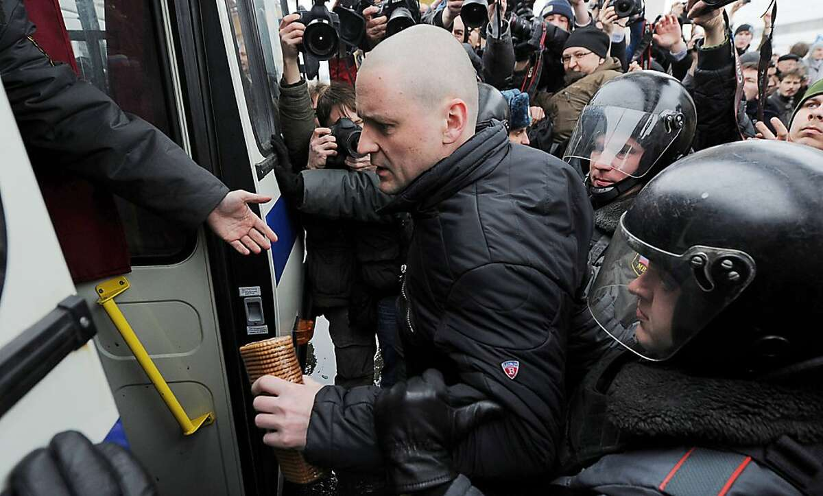 COORECTING BYLINE Russian riot policemen detain an opposition Left Front movement leader, Sergei Udaltsov, during the demonstration outside Ostankino tower which aims to cap a growing campaign for Russians to boycott NTV television, in Moscow on March 18, 2012. Riot police arrested dozens of protesters today who picketed Moscow's iconic television tower after footage purporting to show people being paid to rally against Vladimir Putin was aired nationally. An AFP correspondent saw organisers Boris Nemtsov and Sergei Udaltsov being led away with about 30 others sporting the white protest ribbons of the nascent movement against Putin's 12-year domination of Russia. AFP PHOTO / ANDREY SMIRNOV (Photo credit should read ANDREY SMIRNOV/AFP/Getty Images)