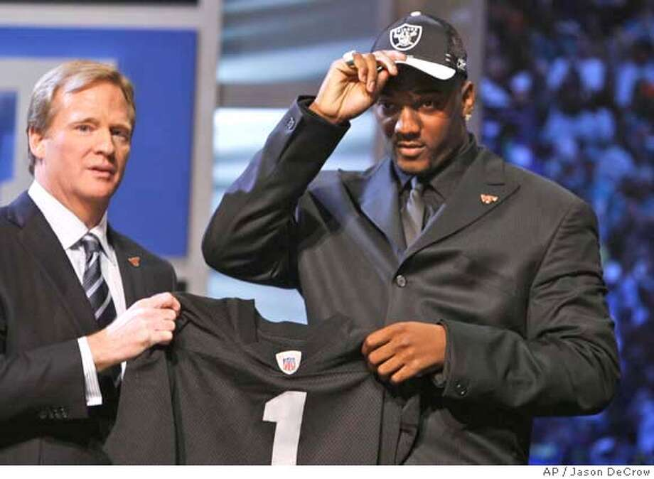 JaMarcus Russell, a quarterback from Louisiana State puts on a cap while standing with NFL commissioner Roger Goodell after being selected by the Oakland Raiders as the No. 1 overall pick in the NFL Draft Saturday, April 28, 2007 at Radio City Music Hall in New York. (AP Photo/Jason DeCrow) Photo: STEPHEN CHERNIN