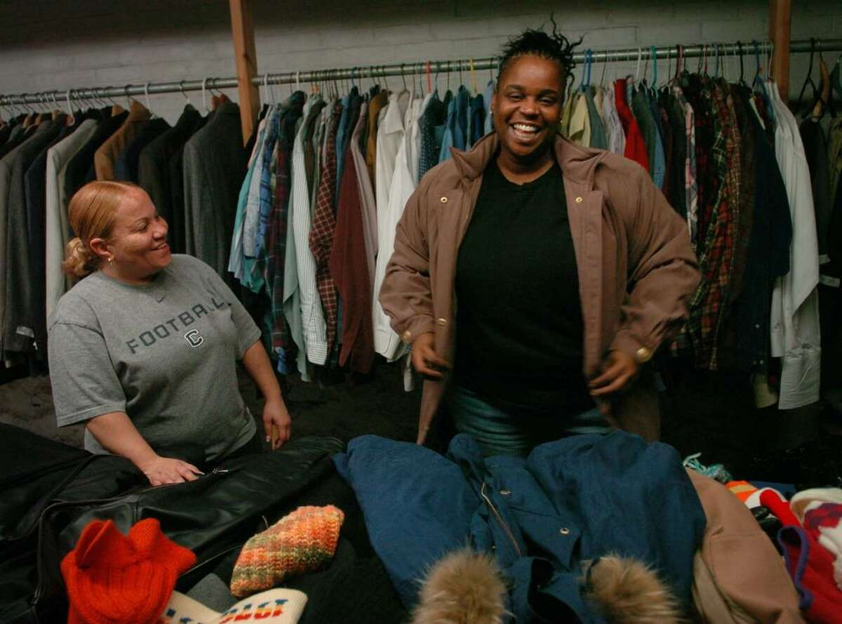 Sidonia Moulton, left of Hartford, and Keisha Forney of Norwalk, residents at the Bridgeport Rescue Mission, organize donated coats for the Mission's annual winter coat giveaway.