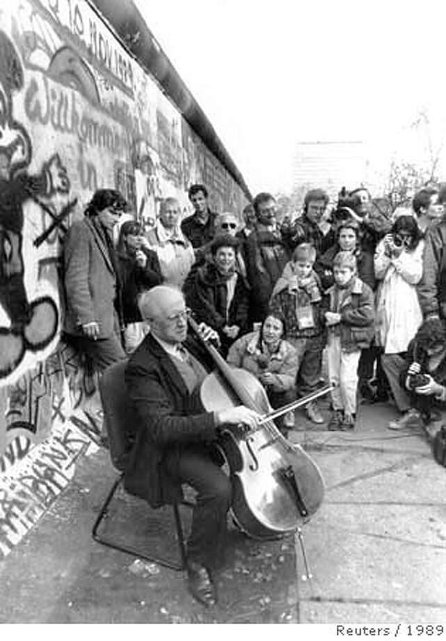 Russian cellist and composer Mstislav Rostropovich is filmed by media as he plays Bach next to the Berlin wall at Checkpoint Charlie, in this November 12, 1989 file photo. Rostropovich, who became an international symbol of the fight for artistic freedom under Soviet rule, died on Friday at the age of 80 a spokeswoman for Russia's state culture agency said. Russian news agencies quoted a source close to the musician as saying that Rostropovich had died in a Moscow hospital after a long illness. REUTERS/ullstein - Succo (GERMANY) B/W ONLY Photo: STR