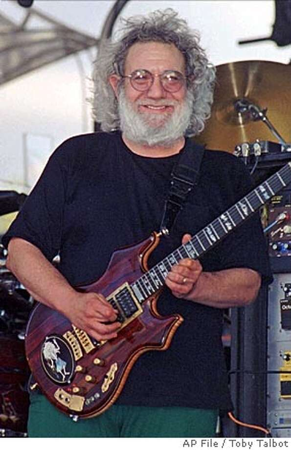 "FILE--Guitarist Jerry Garcia of the Grateful Dead smiles as he plays in Highgate, Vt., in this July 1994 file photo. The legal battle over who will get Garcia's guitars hit another sour note as settlement talks collapsed between Guitar-maker Doug Irwin, who built the instruments, and the band members who played alongside them. ""I drew the line when their lawyer's fine print said that I had to do a joint press conference with the Grateful Dead where I would have to say that I was fully satisfied with the settlement,'' Irwin said in a statement on Dec. 3, 2001. (AP Photo/Toby Talbot, File) ROSEBUD CAT JULY 1994 FILE PHOTO Photo: TOBY TALBOT"