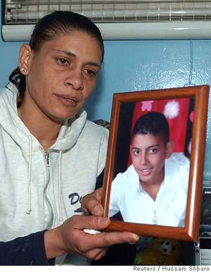 The mother of Ziad Ghandour holds his photograph in Beirut April 26, 2007. Lebanese police found on Thursday, the bodies of a Sunni Muslim government supporter and the 12-year-old boy, Ghandour, whose abduction earlier this week was linked to Lebanon's rising sectarian tension. REUTERS/Hussam Shbaro (LEBANON) 0 Photo: STR