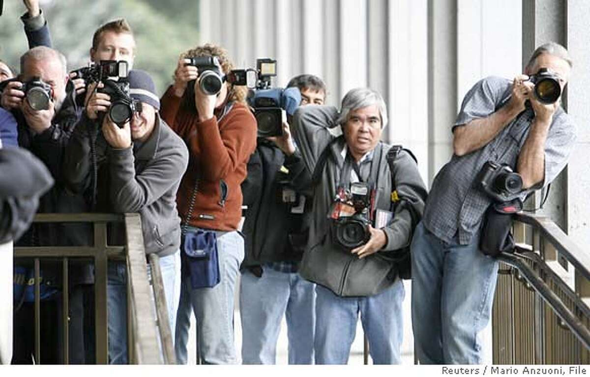 Photographers take pictures of music producer Phil Spector as he arrives for jury selection for his murder trial in Los Angeles April 16, 2007. REUTERS/Mario Anzuoni (UNITED STATES)