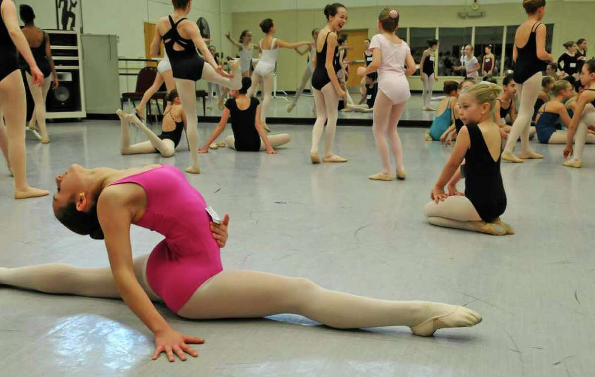 Abigail Grassmyer of Ballston Lake, 8, right, watches Natalie Gasparini of Pleasant Valley, 12, left, as they both warm up prior to the start of the audition for children for the upcoming New York City Ballet performances of Firebird and Romeo + Juliet this summer at SPAC, as the National Museum of Dance on Sunday March 18, 2012 in Saratoga Springs, N.Y. About 200 young dancers tried out. Gasparini got a part. (Philip Kamrass / Times Union )