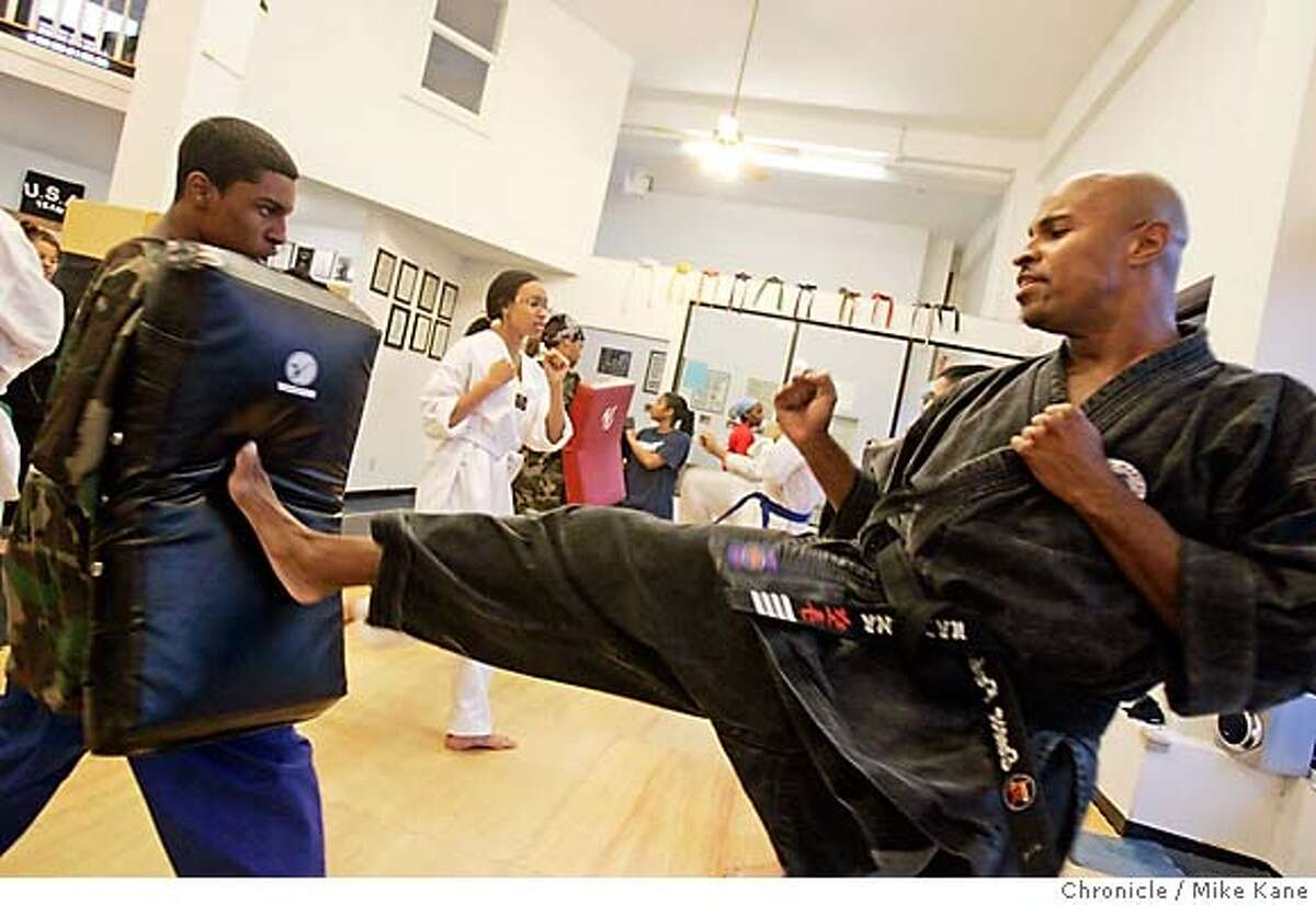 JA_FROHMS_287_MBK.JPG Jefferson Award winner Earnest Frohms, right, demonstrates kicking technique with Jonathan Taylor, 15 of Oakland, left holding pad, in his Karate school, Frohms Martial Arts, in Oakland, CA, on Tuesday, April, 10, 2007. photo taken: 4/10/07 Mike Kane / The Chronicle ** Earnest Frohms, Jonathan Taylor MANDATORY CREDIT FOR PHOTOG AND SF CHRONICLE/NO SALES-MAGS OUT