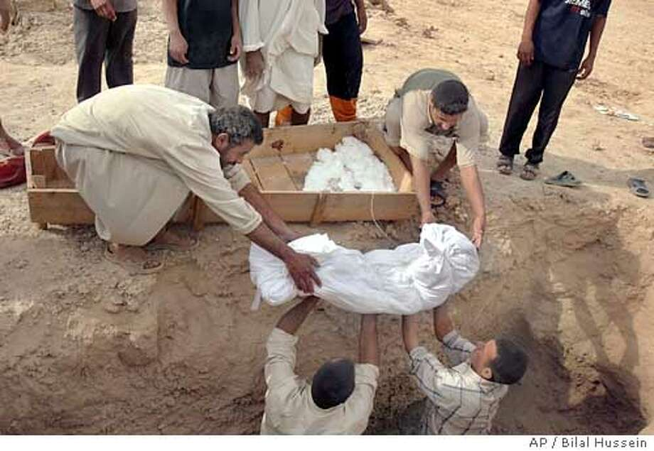 Iraqis lower the body of a US airstrikes victim into the grave in Ramadi, Iraq, Monday Oct. 17 2005, . U.S. warplanes and helicopters bombed two villages near the restive city of Ramadi, killing an estimated 70 militants, the military said Monday, though witnesses said at least 39 of the dead were civilians.(AP Photo/Bilal Hussein) Photo: BILAL HUSSEIN