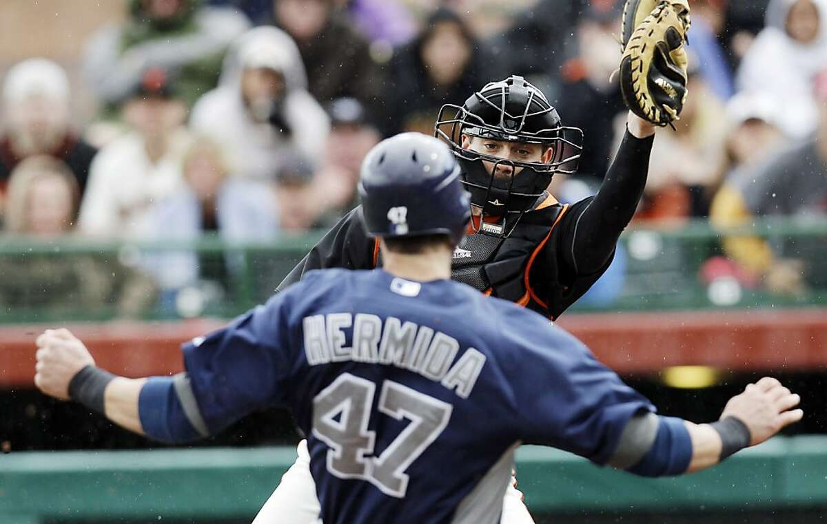 San Francisco Giants catcher Chris Stewart prepares to tag out San Diego Padres' Jeremy Hermida at the plate on a ground ball from Jedd Gyorko during the sixth inning of a spring training baseball game, Sunday, March 18, 2012, in Scottsdale, Ariz. (AP Photo/Marcio Jose Sanchez)