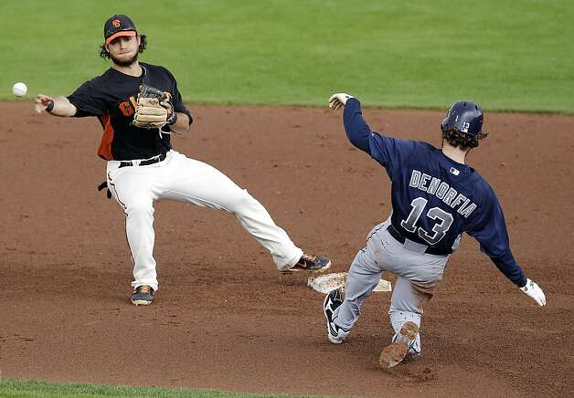 San Francisco Giants shortstop Brandon Crawford, left, turns a double play over San Diego Padres' Chris Denorfia on a ground ball by Jesus Guzman during the fourth inning of a spring training baseball game, Sunday, March 18, 2012, in Scottsdale, Ariz. (AP Photo/Marcio Jose Sanchez) Photo: Marcio Jose Sanchez, Associated Press