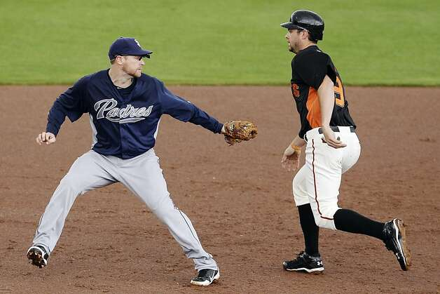 San Diego Padres third baseman Chase Headley, left, tags out San Francisco Giants' Brandon Belt after a ground ball by Justin Christian during the third inning of a spring training baseball game, Sunday, March 18, 2012, in Scottsdale, Ariz. (AP Photo/Marcio Jose Sanchez) Photo: Marcio Jose Sanchez, Associated Press