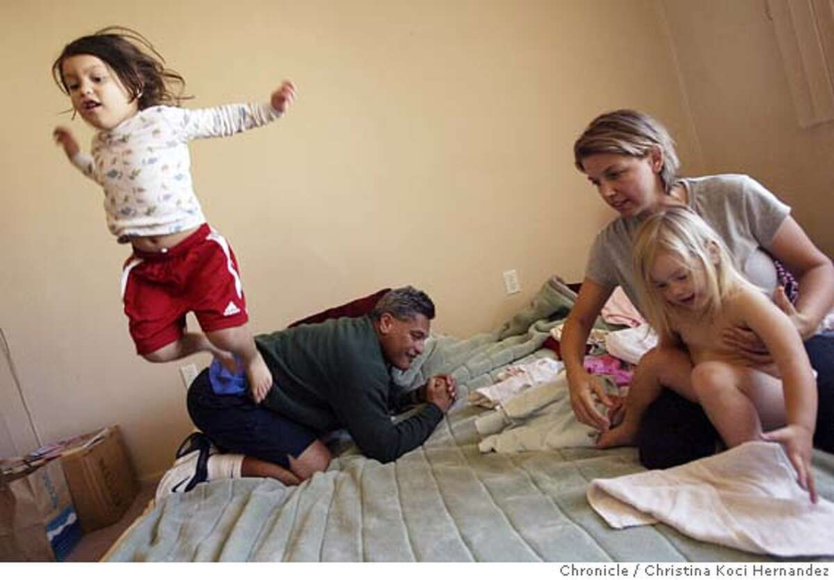 CHRISTINA KOCI HERNANDEZ/CHRONICLE On the bed the whole family shares, Olive,3, jumps-off her dad,(L)Lou Maunupau, 47.(On right) wife Claudia Vlasakova, 37, helps daughter Daisy,2, fold laundry. Lou Maunupau, 47, and wife Claudia Vlasakova, 37. They live in San Francisco's Sunset District, renting. The pay $1,200 a month for a small one bedroom, almost like a studio, for them and their two daughters, Olive is 3, and daisy 2. They have a combined income of a little over $52,000 a year, but find themselves struggling to make ends meet. They are an example of how many Bay Area families living well above the nation's official poverty line find themselves cutting corners to afford the basics of food, housing, transportation and health care.