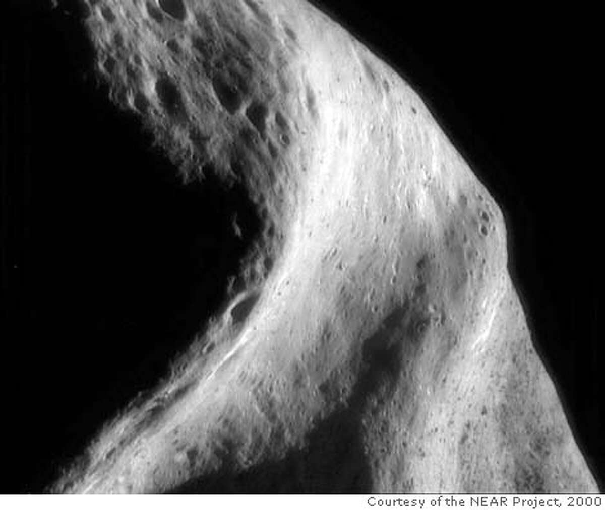 """The South Saddle NEAR Shoemaker's current 100-kilometer (62-mile) orbit gives it a bird's eye view of the asteroid. From this distance, only a handful of pictures are needed to create an image mosaic of a large area. This mosaic of four frames, photographed on September 26, 2000, was taken as the spacecraft looked down on the """"saddle"""" region from the south. The broad, curved depression that stretches vertically across the image is an area of the asteroid that was in shadow during the earlier 100-kilometer orbit, in April 2000. The area that appears speckled at the lower right is the same boulder-rich area featured as the April 4, 2000, Image-of-the-Day. The boulders are easily visible in the full-sized version of today's image. (Mosaic of images 0145364037, 0145363975, 0145363913, 0145363851) Captions and images courtesy of the NEAR Project (JHU/APL)."""
