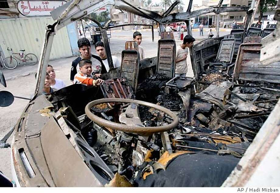 Iraqi kids look at a destroyed mini bus destroyed after a suicide bomber blew himself up in northwest Baghdad, Iraq, Sunday, April 15, 2007. At least 8 people died in the blast and another 11 were wounded, an official at the Khazimiyah Hospital said. (AP Photo/Hadi Mizban) Photo: HADI MIZBAN