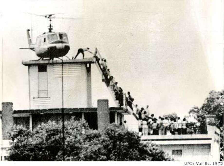 4/29/1975-Saigon: Air America helicopter crewman helps evacuees up the ladder on top of a Saigon Building. The evacuation site is one of many in the downtown area from where American and foreign nationals are being evacauted to waiting Navy ships off the coast (UPI) Photo by Van Es  Ran on: 04-16-2007  The Vietnam War ended with the United States withdrawing its troops and evacuating the capital city of Saigon. Photo: Photo By Van Es