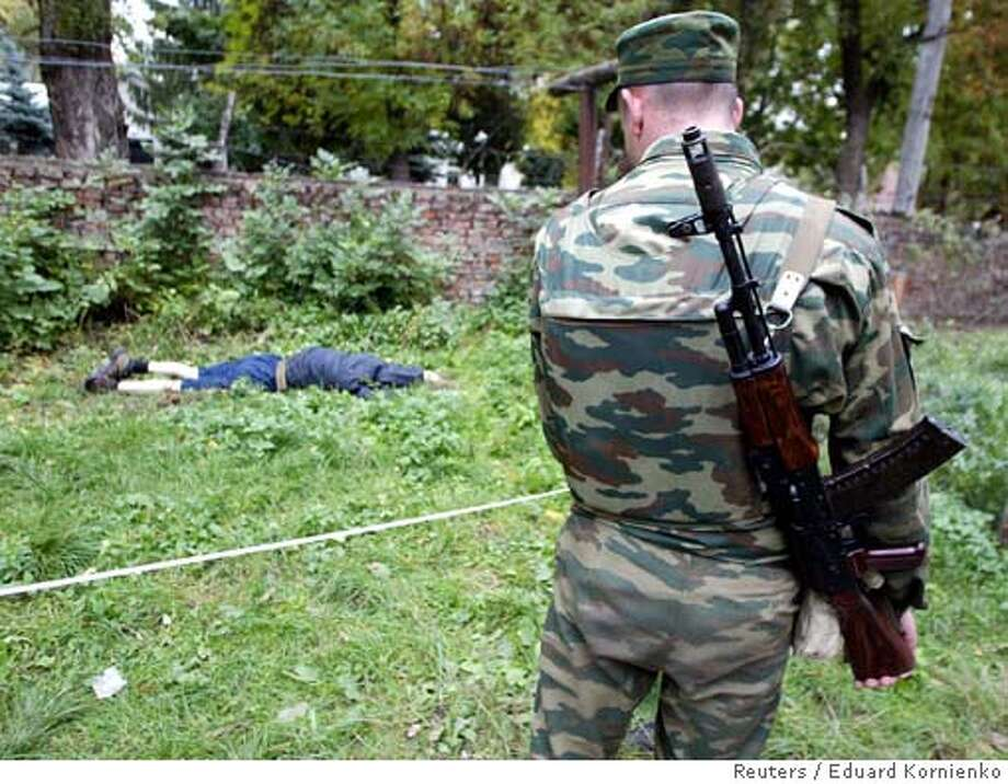 ATTENTION EDITORS - VISUALS COVERAGE OF SCENES OF DEATH AND INJURY  A member of the Russian security forces stands near a body of a dead gunman in Nalchik October 13, 2005. Chechen fighters attacked police and army buildings in a southern Russian town on Thursday in a brazen operation that killed dozens and challenged Kremlin assertions it had the turbulent Caucasus under control. REUTERS/Eduard Kornienko Ran on: 10-14-2005  A Russian soldier looks in the direction of a dead gunman in Nalchik, site of coordinated attacks by Chechen fighters. Photo: EDUARD KORNIENKO