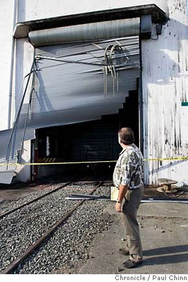 Insurance adjuster Richard Reimche inspects a rollup door which was apparently blown out from the intense heat. ATF agents continue to investigate a warehouse blaze on Oct. 14, 2005 in Vallejo, Calif. More than $100 million in wine, including stock of several well-known Bay Area wineries, was destroyed by a blaze that burned through a former torpedo bunker turned wine warehouse on Mare Island Wednesday. Photo: PAUL CHINN
