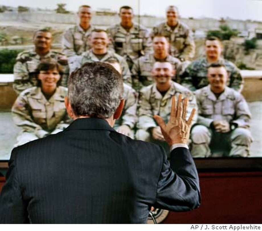 President Bush waves goodbye as he finishes speaking via video teleconference to American troops from the 42nd Infantry Division on duty in Tikrit, Iraq, at the White House in Washington, Thursday, Oct. 13, 2005. (AP Photo/J. Scott Applewhite) Photo: J. SCOTT APPLEWHITE