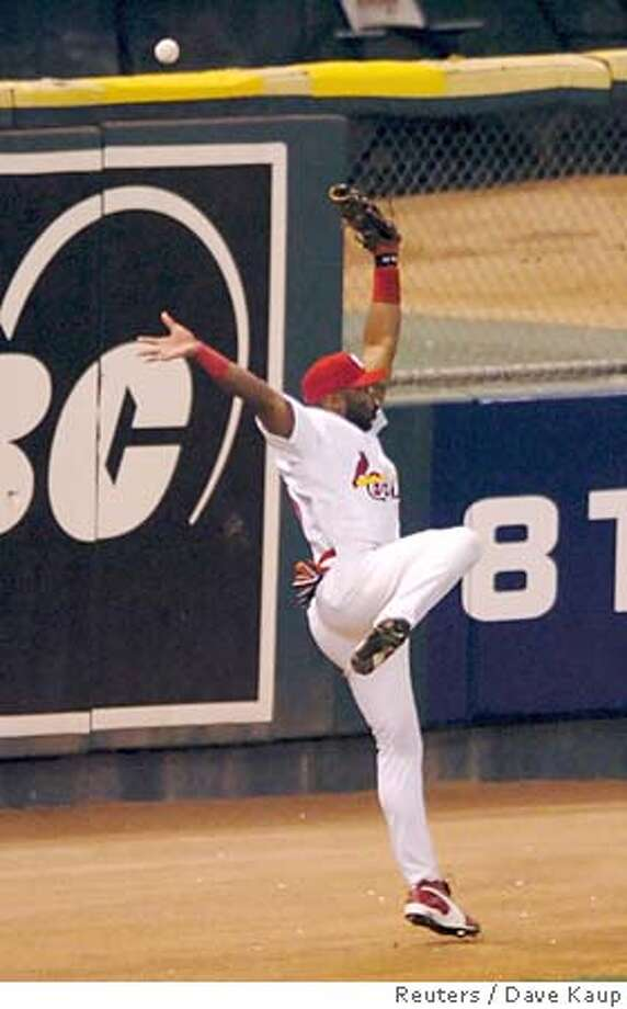 St. Louis Cardinals' Reggie Sanders goes airborne as he tries to make a catch on a RBI triple off the bat of Houston Astros' Adam Everett during the eighth inning in Game 2 of the National League Championship Series in St. Louis, Missouri, October 13, 2005. Sanders was shaken up on the play and left the game. REUTERS/Dave Kaup Ran on: 10-14-2005  Photo caption Photo: DAVE KAUP