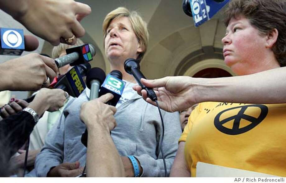 Peace activist Cindy Sheehan, left, talks with reporters after delivering a letter to Gov. Arnold Schwarzenegger's Sacramento office demanding that he withdraw the National Guard from Iraq, Wednesday, Oct. 12, 2005. Sheehan, whose son Casey was killed in Iraq a year ago, camped outside President Bush's ranch in Texas for 28 days in August to protest U.S. policy in Iraq. At right is Sheehan's sisiter, Dede Miller.(AP Photo/Rich Pedroncelli) STAND ALONE Photo: RICH PEDRONCELLI