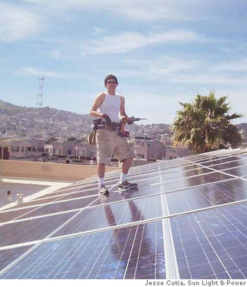 Mission Plaza Apartments. Installer Becca Litke puts the finishing touches on solar array. Photo: Jesse Cutia, Sun Light And Power