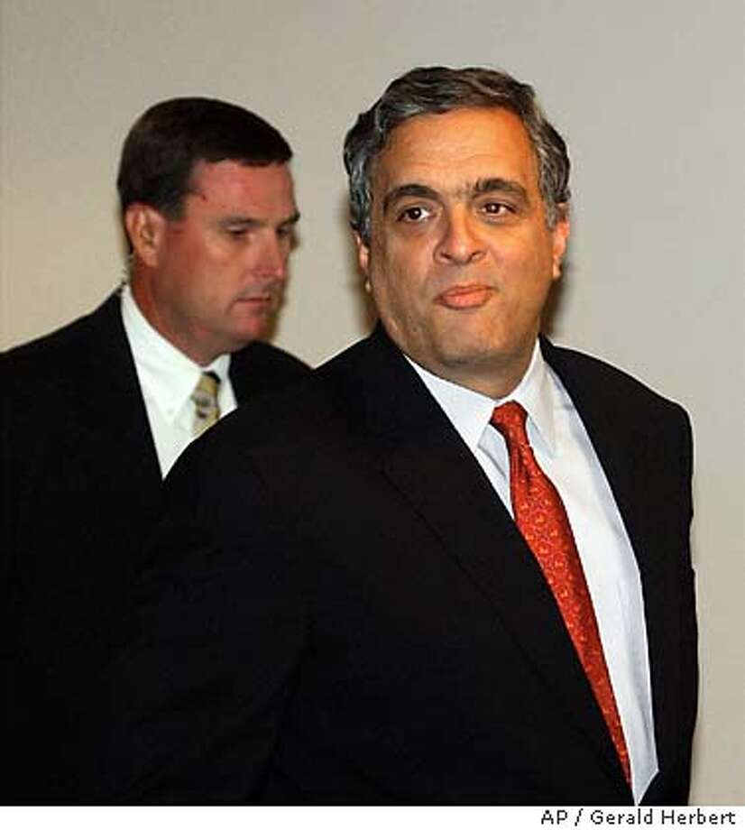 CIA director George Tenet leaves a closed Senate Intelligence hearing on Capitol Hill in Washington Wednesday, July 16, 2003. Man in background is unidentified. Tenet was testifying about President Bush's claim in his State of the Union address that Iraq was trying to buy uranium in Africa to restart its nuclear weapons program. (AP Photo/Gerald Herbert) (AP Photo/Gerald Herbert) Photo: GERALD HERBERT