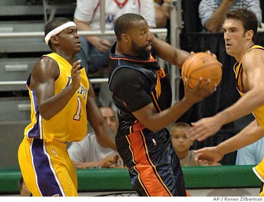 Golden State Warriors' Baron Davis, center, is double-teamed by Los Angeles Lakers' William Parker, left, and Chris Mihm during a preseason game in Honolulu, Hawaii, Tuesday, Oct.11, 2005. (AP Photo/Ronen Zilberman) Photo: RONEN ZILBERMAN