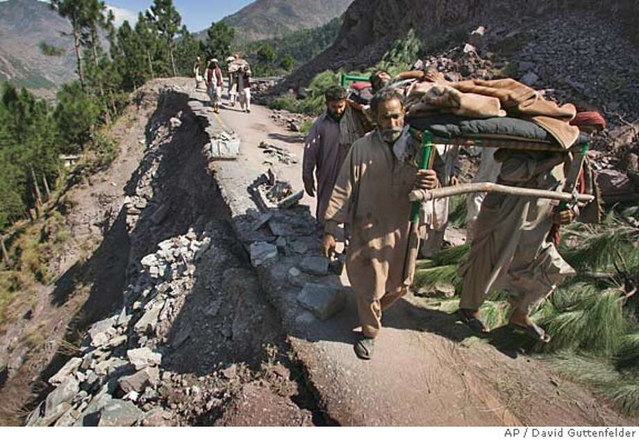 Pakistani men carry an injured man in a bed as they walk on an earthquake damaged mountain road near the village of Sanger, Pakistan, Wednesday Oct. 12, 2005. Across the region of northwest Pakistan, destroyed by an earthquake, hundreds of villages remain cut off from help. (AP Photo/David Guttenfelder) FOR STORY SLUGGED PAKISTAN QUAKE MOUNTAIN VILLAGE Photo: DAVID GUTTENFELDER