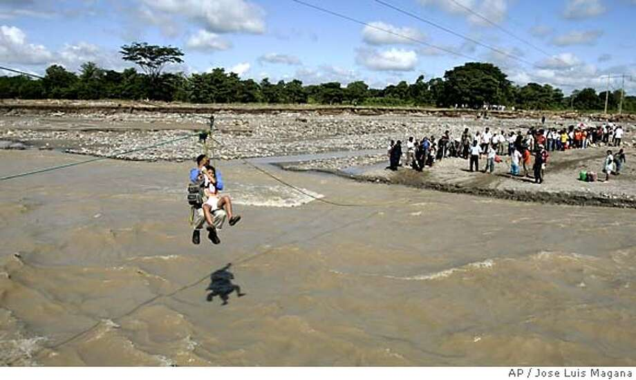 People use cable lines to cross over the Coatan river which overflowed from rains from Hurricane Stan in Tapachula the southern state of Chiapas, Mexico, Oct. 11, 2005. (AP Photo/Jose Luis Magana) **EFE OUT** Photo: JOSE LUIS MAGANA